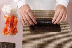 Cocinero que hace los rodillos de sushi con los salmones Imágenes de archivo libres de regalías