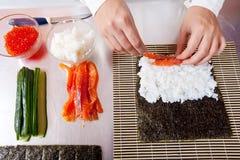 Cocinero que hace los rodillos de sushi japoneses Imagen de archivo