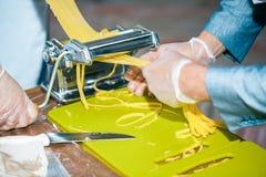 Cocinero que hace los tallarines de los espaguetis con la máquina de las pastas en la tabla de cocina fotos de archivo libres de regalías