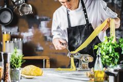 Cocinero que hace los tallarines de los espaguetis con la máquina de las pastas en la tabla de cocina con algunos ingredientes al imagen de archivo