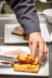 Cocinero que hace un plato del almuerzo Imagenes de archivo