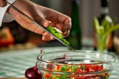 Cocinero que hace una ensalada con las cebollas Imagen de archivo