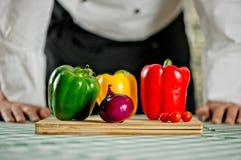 Cocinero que hace una ensalada con las cebollas Fotografía de archivo