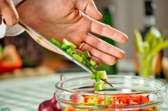 Cocinero que hace una ensalada con las cebollas Fotos de archivo libres de regalías