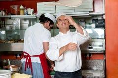 Cocinero que lanza la pasta de la base de la pizza imagen de archivo libre de regalías