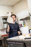 Cocinero que lanza la pasta mientras que hace los pasteles Fotografía de archivo libre de regalías