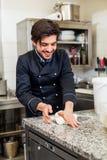 Cocinero que lanza la pasta mientras que hace los pasteles Imagenes de archivo