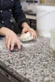 Cocinero que lanza la pasta mientras que hace los pasteles Foto de archivo libre de regalías