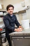Cocinero que lanza la pasta mientras que hace los pasteles Fotos de archivo