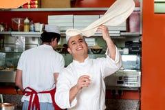 Cocinero que lanza para arriba ligeramente la pasta baja Fotos de archivo