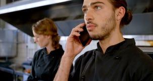 Cocinero que mira el tablero mientras que habla en el teléfono móvil 4k