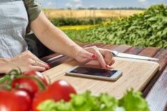 Cocinero que mira smartphone de la receta Fotos de archivo libres de regalías