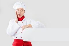 Cocinero que muestra la muestra en blanco Control de la sorpresa del cocinero, del panadero o del cocinero de la mujer Fotografía de archivo libre de regalías