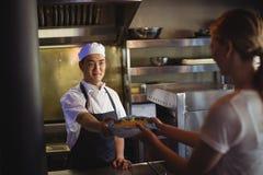 Cocinero que pasa la bandeja con las patatas fritas a la camarera Foto de archivo