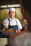 Cocinero que pasa la bandeja con las patatas fritas a la camarera Foto de archivo libre de regalías