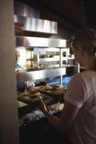 Cocinero que pasa la bandeja con las patatas fritas y la hamburguesa a la camarera Foto de archivo