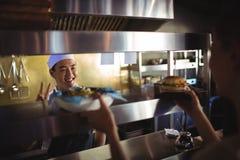 Cocinero que pasa la bandeja con las patatas fritas y la hamburguesa a la camarera Fotografía de archivo libre de regalías