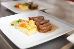 Cocinero que platea encima de la comida en un restaurante foto de archivo