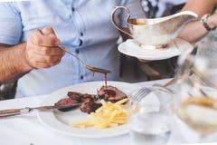 Cocinero que platea encima de la comida en un restaurante que vierte una salsa o una salsa sobre la carne antes de servirla al cl Imagen de archivo
