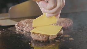 Cocinero que pone dos pedazos de queso en la chuleta para la hamburguesa en parrilla eléctrica metrajes