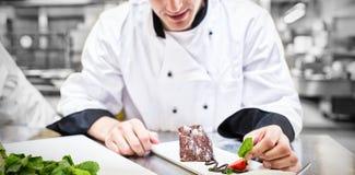 Cocinero que pone la hoja de la menta con su postre Imagen de archivo libre de regalías