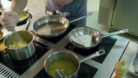 Cocinero que pone pescados floured en sartenes mientras que otros patatas de trituración del cocinero metrajes