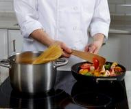 Cocinero que prepara diversos platos Fotografía de archivo libre de regalías
