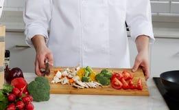 Cocinero que prepara diversos platos Foto de archivo libre de regalías