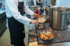 Cocinero que prepara el alimento en la cocina Imágenes de archivo libres de regalías