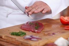 Cocinero que prepara el filete Fotos de archivo