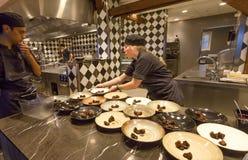 Cocinero que prepara la comida en el kitchene abierto del restaurante, en el centro cultural Fotografiska Imagen de archivo libre de regalías