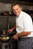 Cocinero que prepara la comida en la cocina en cocina Imagen de archivo