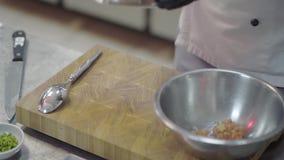 Cocinero que prepara los mariscos en una cocina moderna del restaurante Manos masculinas que mezclan el atún cortado en cuenco pr metrajes