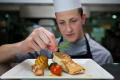 Cocinero que prepara una comida con los salmones Foto de archivo libre de regalías