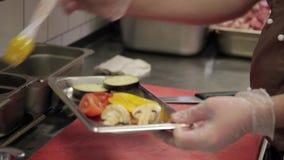 Cocinero que prepara verduras para freír en parrilla en cocina moderna del restaurante almacen de metraje de vídeo