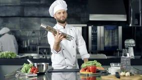 Cocinero que presenta en el restaurante de la cocina Cocinero que calienta con el pimentero en el lugar de trabajo almacen de video