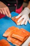 Cocinero que quita el hueso de pescados imagenes de archivo