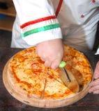 Cocinero que rebana la pizza Imágenes de archivo libres de regalías
