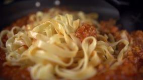 Cocinero que revuelve los espaguetis y la salsa metrajes