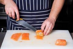 Cocinero que rueda encima de los filetes de color salmón Fotografía de archivo libre de regalías
