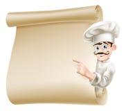 Cocinero que señala en el menú Imágenes de archivo libres de regalías