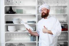 Cocinero que se coloca al lado de estantes con los platos y que sostiene una botella de champán para sus visitantes Fotografía de archivo