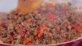 Cocinero que se mezcla friendo la carne de tierra con las cebollas y los tomates cortados metrajes
