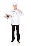 Cocinero que sostiene el pote y la cuchara del acero inoxidable Fotografía de archivo