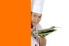Cocinero que sostiene pescados sin procesar en una placa verde Fotografía de archivo libre de regalías