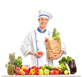 Cocinero que sostiene un tomate y un bolso detrás de un vector lleno de frutas y Fotos de archivo