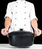 Cocinero que sostiene una cazuela hacia, sobre la tabla blanca Imágenes de archivo libres de regalías