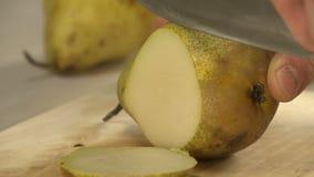 Cocinero que taja la pera para cocinar el postre almacen de video