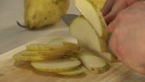 Cocinero que taja la pera para cocinar el postre almacen de metraje de vídeo