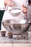 Cocinero que tamiza la harina Foto de archivo libre de regalías